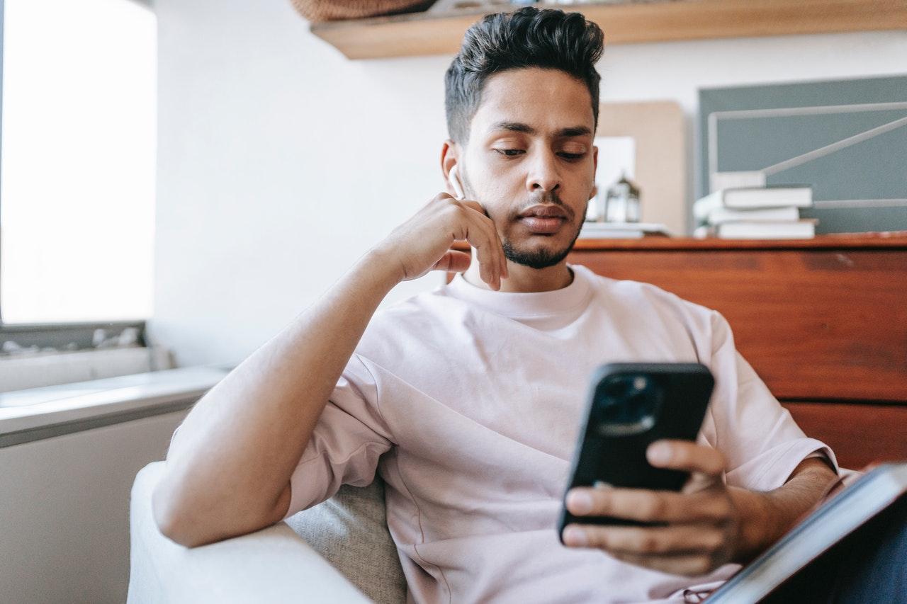 A man sat down looking at his phone